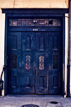 Large double doorway along the streets of the French Quarter in New Orleans, Louisiana. Old wooden doors with wrought iron windows.