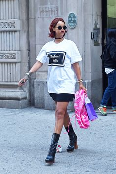 "Rihanna makes a statement in style with a ""School Kills"" emblazoned T-shirt, mini-skirt, and platform boots. We hail this look ""punk luxe.""   - HarpersBAZAAR.com"
