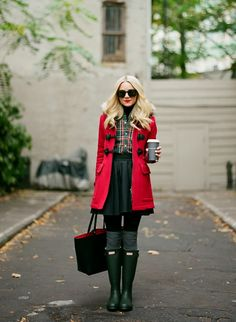 Red Coat with black goggles, plaid top, black skirt with black tights and grey thigh high socks and hunter boots.