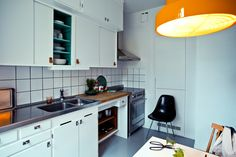 White cabinets, white tile with dark grout, steel appliance and vent hood