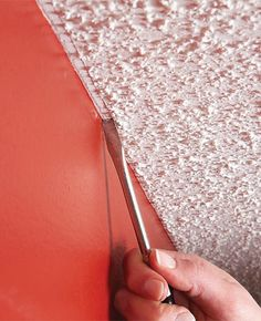 Drag a flat-head screwdriver along the popcorn ceiling to make getting a straight line possible. (Would rather get ride of the popcorn!)