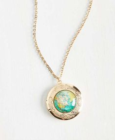 This gorgeous map necklace with locket pendant, antiqued gold rim, and colourful print will have you dreaming of far-off destinations.