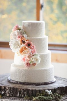 white dotted cake with a cascade of florals by http://www.classiccakesbylori.com | Photography by carolinejoy.com |  Read more - http://www.stylemepretty.com/2013/06/27/austin-wedding-from-caroline-joy-photography-2/