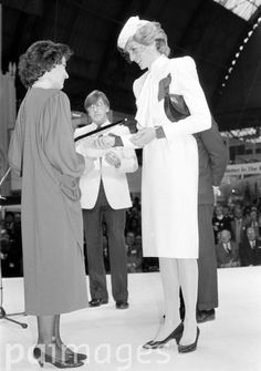 November 27, 1985:  Princess Diana wearing a dress by designer Bruce Oldfield, presenting a prize in the holiday poster competition to Austria, during the World Travel Market at Olympia in London. The Princess had earlier officially opened the market, which is the travel industry's top trade exhibition.