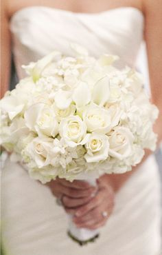 White roses, stephanotis, calla lily and hydrangea bouquet. The stems are tied with an ivory satin ribbon.