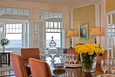 A bright and airy traditional dining room is the perfect spot to enjoy family dinners in this coastal home. Soft yellow walls and white windows make for an inviting, seaside experience. Comfy, burnt orange chairs round the dining table where a bouquet of yellow roses are displayed as the centerpiece.