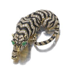 ENAMEL, EMERALD AND DIAMOND BROOCH, DAVID WEBB Designed as a resting tiger, set with brilliant- and single-cut diamonds, pear-shaped emeralds and decorated with black enamel