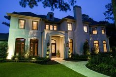 Lots of windows, beautiful double door entry, gorgeous entry lanterns, spiral topiaries & neutral palette.