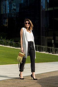 Look Modern & fashionable, maxi colete, calça jogging, scarpin preto e bolsa de franjas. Executive style!