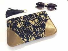 Very important !!!!!!!! This listing is only for the fabric clutch,all other items shown are simply for display purposes!!!!!!!!! This black and gold fabric clutch is a stylish way for carrying all your everyday essentials.Fits easily your keys,wallet,mobile or small cosmetic products.  Use it as an everyday clutch, or for storing your make-up products. Its the perfect pouch to use on a trip in town, the beach or anywhere else you feel like using it. :) I strongly believe that the inside of…