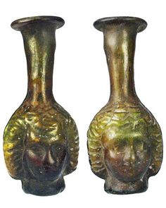 Roman artifacts glass Flask :    Golden amber mold-blown Janus glass head flask, the faces similar to either side, rolled rim, some iridescence and encrustation. Janus was the Roman God of beginnings and endings.  50 - 100 AD