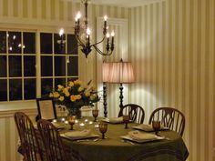Thanksgiving Simplicity, simple cream and yellow roses in a clear vase.Green and brown table cloth, votives.