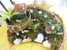 My fairy garden, made it in a broken clay pot bottom