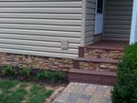 Before-and-after photos prove that faux stone mobile home skirting can beautify the foundation of any home.