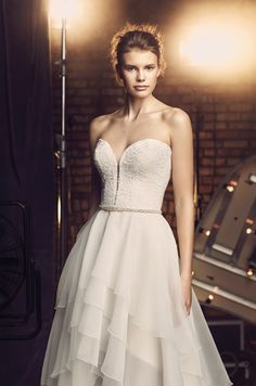 @mikaellabridal | Style 2084, Mikaella Lace and Organza #WeddingDress. Lace strapless plunging neckline bodice. Multiple tiered organza high-low skirt. Removable beaded belt at waist. Swarovski buttons along center back bodice. Visit our website to see the entire gown!