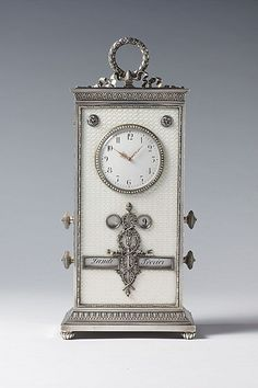 rge Imperial guilloché enamelled desk clock and calendar by Fabergé, of rectangular upright form, enamelled translucent opalescent oyster white over a guillochage, centred to the top by a circular pearl set bezel, with a flaming silver torch entwined by laurels, surmounted by a laurel wreath tied with a bow. Workmaster: Johann Victor Aarne, St. Petersburg, pre 1896. Purchased by the Dowager Tsarina Maria Feodorvona from Fabergé's St. Petersburg shop on 9th March 1898 for 600 roubles.