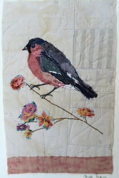I treasure the old and worn and refashion them into little textile collages in my attic studio in a converted manse in Northumberland, England. Everything I make is individual and unique. This little bull finch is hand appliquéd and embroidered on to a support of an old quilt coverlet fragment. You can see very faded pieces of print within the patchwork. There is a little pink edge at the bottom which is a piece unpicked from another quilt. The bull finch is sitting on an embroidered branch…