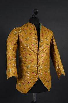 Long-sleeved at-home waistcoat, ca. 1780-1790. Glazed cotton, block printed with a design of naturalistic flower sprays on light brown ground, fabric-covered buttons; quilted green silk taffeta lining.