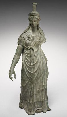 A Roman bronze figure of Isis-Fortuna   Circa 1st-2nd Century A.D.  The goddess depicted striding forward, wearing a short-sleeved chiton over which a fringed himation is draped and secured by the typical knot, the separately-made right arm lowered, the left arm now missing, the long tresses falling over her shoulders, surmounted by a crescentic diadem and a modius, 7in (18cm) high