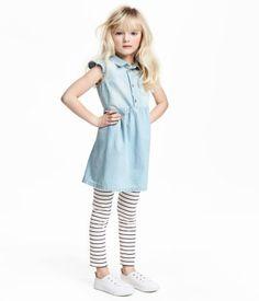 Ljus denimblå. Ett set med klänning och leggings. Klänningen är i mjuk, vävd bomullskvalitet. Den har krage och knäppning upptill. Bröstficka och kort