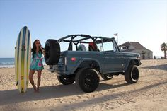 Green open top Ford Bronco with 60s girl with surfboard