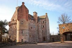 A restored 12th century Scottish castle in the United Kingdom, with clawfoot tubs, gardens, medieval woodwork and stonework, and a great room for dining.