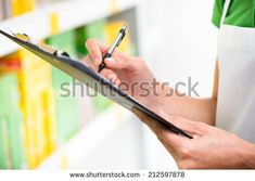 Supermarket clerk at work holding pen and clipboard with shelf on background, hands close-up.