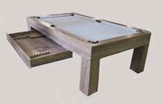Modern billiard table in natural finish walnut, with built-in accessory drawer.
