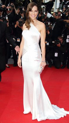 HILARY SWANK Swank hit the red carpet in a stunning Atelier Versace one-shoulder gown that featured a draped back. The actress finished her look with sapphire Chopard jewels, Jimmy Choo sandals, and a statement clutch.