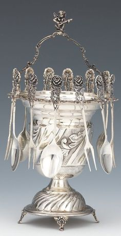 Sterling silver basket/vase with a handle, raised on a domed base with four feet, cherub finial on the handle; featuring suspended 800 silver teaspoons and forks.