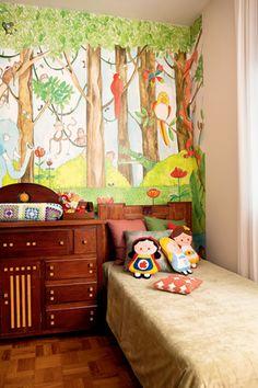 O papel de parede Jungle Dudes, da marca Mr Perswall, foi   comprado pela internet e cobre toda a parede atrás da cômoda.  Sobre a manta, da Paola da Vinci, almofadas, da Tamtum,   e bonecas de feltro, da Panaceia