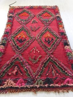 Authentic Talsint Berber vintage rug. Amazing color palette, this rug have a soul. Excellent condition.  ******  COCO Berber wool rug:  * Size : 5 1 x 8 4 (155 cm x 255 cm). * Color : Red as dominant tone, with pink, purple, olive green and grey motifs * Age : 40-45 years old * Condition : Excellent. * Material : Wool  * As all vintage products, this rug can present small imperfections or discolorartions, due to its age.  * As all items selected by SunnyHomeStory, this rug is cleaned, washed…