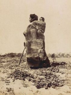 Portrait of unidentified Aboriginal woman wearing a possum skin cloak, carrying a child on her back, South Australia, ca. National Library of Australia.