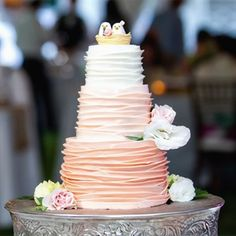 The three-tiered cake feature a ruffled ombré design with fresh flowers tucked into the tiers.