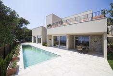 Destacan los grandes ventanales y la piscina rectangular que sirve de nexo de unión entre la casa y el mar. #casadeverano #costabrava #casaconpiscina