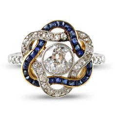 Edwardian sapphire and diamond cluster ring, designed as brilliant-cut diamond and calibré-cut sapphire entwined ribbons centering on a single circular-cut diamond collet, rose-cut diamond three-stone shoulders to the platinum and gold mount
