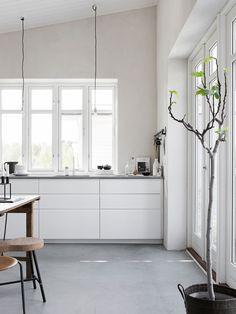 Köket är IKEAs Voxtorp med infällda grepplister för ett minimalistiskt uttryck. Bänkskivan i Silestone Cygnus från House of design. Lampor från Frama. Fikonträd i planteringssäck från Bacsac. Väggfärgen är Fresco kalkfärg i nyansen Bone från Pure & Original. Foto: Sara Medina Lind