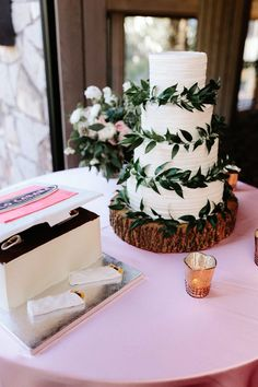 Simple rustic elegant wedding cake with greenery and a wood slice cake stand (Gloria Goode Photography)