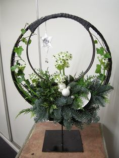 bloemstuk in een frame van 2 ringen in elkaar op standaard, ook leuk om in de kleine ring een kerstbal of waxinehouder te hangen