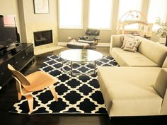 Make Your Room More Standout With These Gorgeous Rugs : Appealing Black and White Geometric Rug in Gorgeous Living Room with Glass Top Round Coffee Table and Attractive Corner Fireplace also Black Leather Lounge Chair