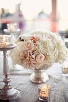 i really like the silver vase/base with pale pink/white flowers together. I want short and full arrangements throughout the table along with the candles.