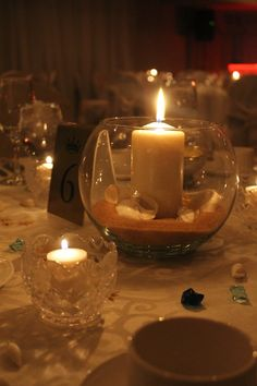 """Romantic Beach themed centerpiece: Glass bowl with """"sand"""", sea shells and candle. Event by: MJ Weddings & Events (mjweddings.com)"""