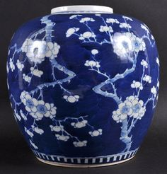 A 19TH CENTURY CHINESE BLUE GLAZED GINGER JAR bearing Kangxi marks to base, painted with flowering prunus. 8.75ins high.