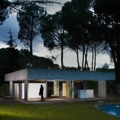 Surrounded by pine trees on the outskirts of Madrid, this concrete structure by FRPO provides shelter and cooking facilities beside a swimming pool