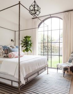 Lovely bedroom features a metal canopy bed, Oly Studio Marco Bed, dressed in soft white bedding and pink and gray ikat pillows as well as a pink ikat bolster pillow placed atop a beige and navy striped rug illuminated by glass vintage barn wall sconces and a Suzanne Kasler Morris Lantern.