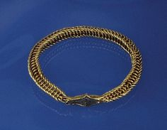 Circular gold arm-ring made of thin plaited rods forming an open-work frame around a single broader rod at its centre. The ends are encased in gold sheet, forming a lozenge-shaped plate with an incised contour line, which has a punched dot in each corner and a cross of five dots at the centre.  9th cent.  Ireland.  Photo credit - British Museum
