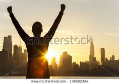 Silhouette of a successful woman or girl arms raised celebrating at sunrise or sunset in front of the New York City Skyline - stock photo