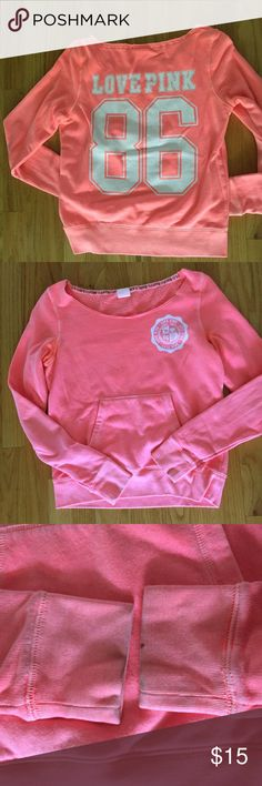 Victoria's Secret pink crewneck Neon coral Victoria's Secret pink crewneck sweatshirt with front pocket. Cutoff/off the shoulder design. White lettering. Size small. Small stains on cuffs. PINK Victoria's Secret Tops Sweatshirts & Hoodies