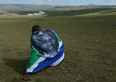 Remembering Madiba | Mnikelo Ndagankulu is draped in a flag as he sits on a hill overlooking the place where Nelson Mandela will be laid to rest in Qunu. Photo: ROBERTO SCHMIDT/AFP