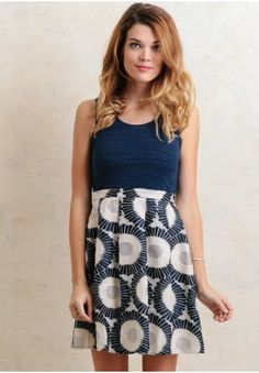 Featuring a heather navy bodice and abstract patterned skirt with embroidered accents and a pleated design, this dress is finished with an exposed silver-toned zipper at the back.